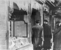 Germans pass by the smashed windows of a Jewish-owned shop.