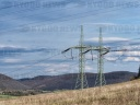 Double mast, power lines, wooded hills, sky with clouds