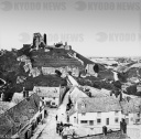 A black and white historic image of a city with a landmark on a hilltop