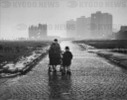 Mother and children walk along deserted cobbled street