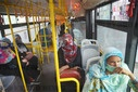 People wearing face masks travel in a Metrobus