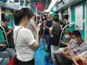 People look at their smartphones on the subway in Hefei, China - 13 Aug 2020