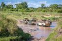 Game viewers carrying tourist drive through a stream in Maasai Mara National Reserve